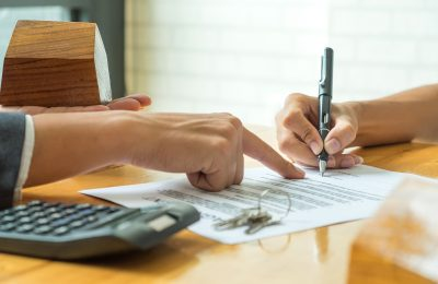 Buyers are signing a home purchase agreement from a broker,model house in broker hand and calculator with a house key on the table.